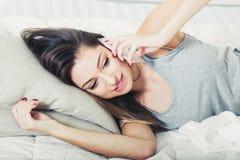 Jeune femme dans la chambre à coucher avec le portrait de téléphone portable Photos libres de droits