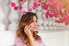Jeune femme dans la chemise rouge parlant au téléphone portable Photo libre de droits