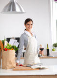 Jeune femme dans la cuisine avec des verres d'un vin Images libres de droits