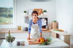 Jeune femme dans la cuisine préparant un aliment Jeune femme dans la cuisine Photos stock