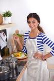Jeune femme dans la cuisine préparant un aliment Jeune femme dans la cuisine Photos libres de droits