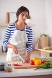 Jeune femme dans la cuisine préparant un aliment Jeune femme dans la cuisine Images stock