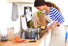 Jeune femme dans la cuisine préparant un aliment Image stock