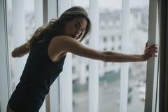 Jeune femme dans la fenêtre se tenante prêt de sous-vêtements dans la chambre images libres de droits