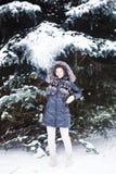 Jeune femme dans la forêt d'hiver ayant l'amusement avec la neige Photos stock