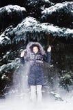 Jeune femme dans la forêt d'hiver ayant l'amusement avec la neige Images libres de droits