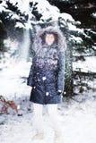 Jeune femme dans la forêt d'hiver ayant l'amusement avec la neige Image stock