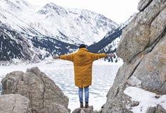 Jeune femme dans la guêpe avec la position tendue par bras sur la roche dans les montagnes d'hiver photographie stock libre de droits