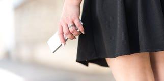 Jeune femme dans la jupe noire avec le téléphone portable dans sa main photos stock