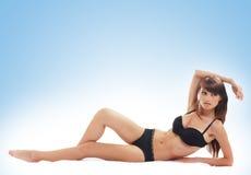 Jeune femme dans la lingerie noire sur un fond bleu Photographie stock
