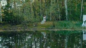 Jeune femme dans la lingerie se tenant sur le bord de mer près de la forêt d'automne banque de vidéos