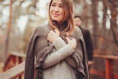Jeune femme dans la marche chaude confortable de cardigan extérieure dans la forêt d'automne, avec l'ami sur le fond Images libres de droits