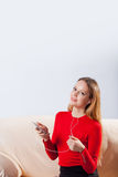 Jeune femme dans la musique de écoute d'écouteurs détendant à la maison dessus ainsi Photos libres de droits