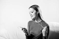 Jeune femme dans la musique de écoute d'écouteurs détendant à la maison dessus ainsi Image stock