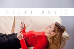 Jeune femme dans la musique de écoute d'écouteurs détendant à la maison dessus ainsi Image libre de droits