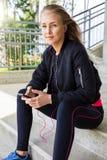 Jeune femme dans la musique de écoute de vêtements de sport sur Smartphone photo stock