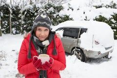 Jeune femme dans la neige avec le véhicule Photographie stock