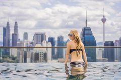Jeune femme dans la piscine ext?rieure avec la vue de ville en ciel bleu Personnes riches photos stock