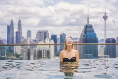 Jeune femme dans la piscine ext?rieure avec la vue de ville en ciel bleu Personnes riches images libres de droits