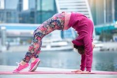 Jeune femme dans la pose de pont contre la ville et la rivière Photo libre de droits