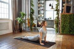 Jeune femme dans la pose de pratique de yoga d'équilibre de homeware sur le tapis dans sa chambre à coucher confortable Image libre de droits