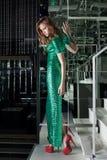 Jeune femme dans la promenade verte de robe de mode sur des escaliers Image stock