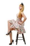 Jeune femme dans la rétro robe florale, se reposant sur des selles Images stock