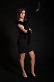 Jeune femme dans la rétro robe sur un fond noir photo stock
