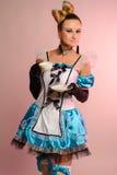 Jeune femme dans la robe érotique Alice au pays des merveilles sur un fond rose Photographie stock libre de droits