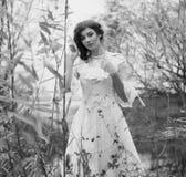 Jeune femme dans la robe blanche dans la forêt noire et blanche Photos stock