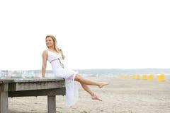 Jeune femme dans la robe blanche se reposant à la plage Photographie stock