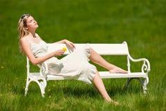 Jeune femme dans la robe blanche se reposant sur le banc blanc Photographie stock libre de droits
