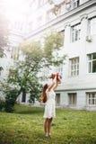 Jeune femme dans la robe blanche tenant son bébé Images stock