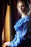 Jeune femme dans la robe bleue de vintage tenant la fenêtre proche dans le coupé Images stock