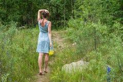 Jeune femme dans la robe bleue romantique avec les fleurs jaunes pendant le MOIS Images stock