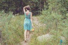 Jeune femme dans la robe bleue romantique avec les fleurs jaunes pendant le MOIS Photographie stock libre de droits