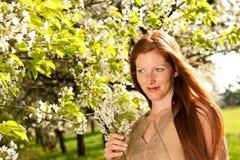 Jeune femme dans la robe brune sous l'arbre de floraison Images libres de droits