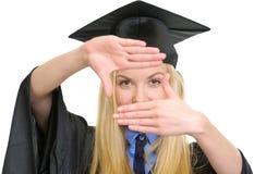 Jeune femme dans la robe d'obtention du diplôme encadrant avec des mains Photos libres de droits