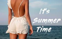 Jeune femme dans la robe d'?t? se tenant sur une plage et regardant ? la mer photos stock