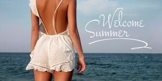 Jeune femme dans la robe d'?t? se tenant sur une plage et regardant ? la mer photographie stock