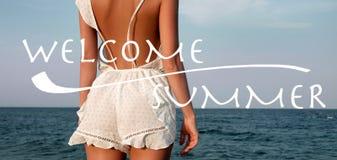 Jeune femme dans la robe d'?t? se tenant sur une plage et regardant ? la mer images stock