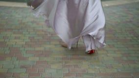 Jeune femme dans la robe et les promenades et entourer de chaussures banque de vidéos