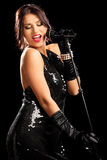 Jeune femme dans la robe noire pendant un concert Image stock