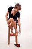 Jeune femme dans la robe noire se reposant sur la chaise et essayant d'augmenter Photos stock