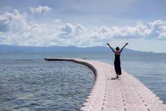 Jeune femme dans la robe noire sur la jetée en mer Photo stock
