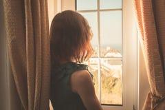 Jeune femme dans la robe regardant la fenêtre photo stock