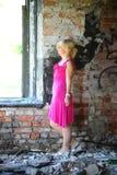 Jeune femme dans la robe rose parmi les ruines Images stock