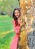 Jeune femme dans la robe rose, se tenant derrière l'arbre regardant vers le bas, le su photographie stock