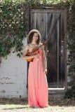 Jeune femme dans la robe rose tenant le violon dehors Images libres de droits