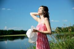 Jeune femme dans la robe rouge au lac Photographie stock libre de droits